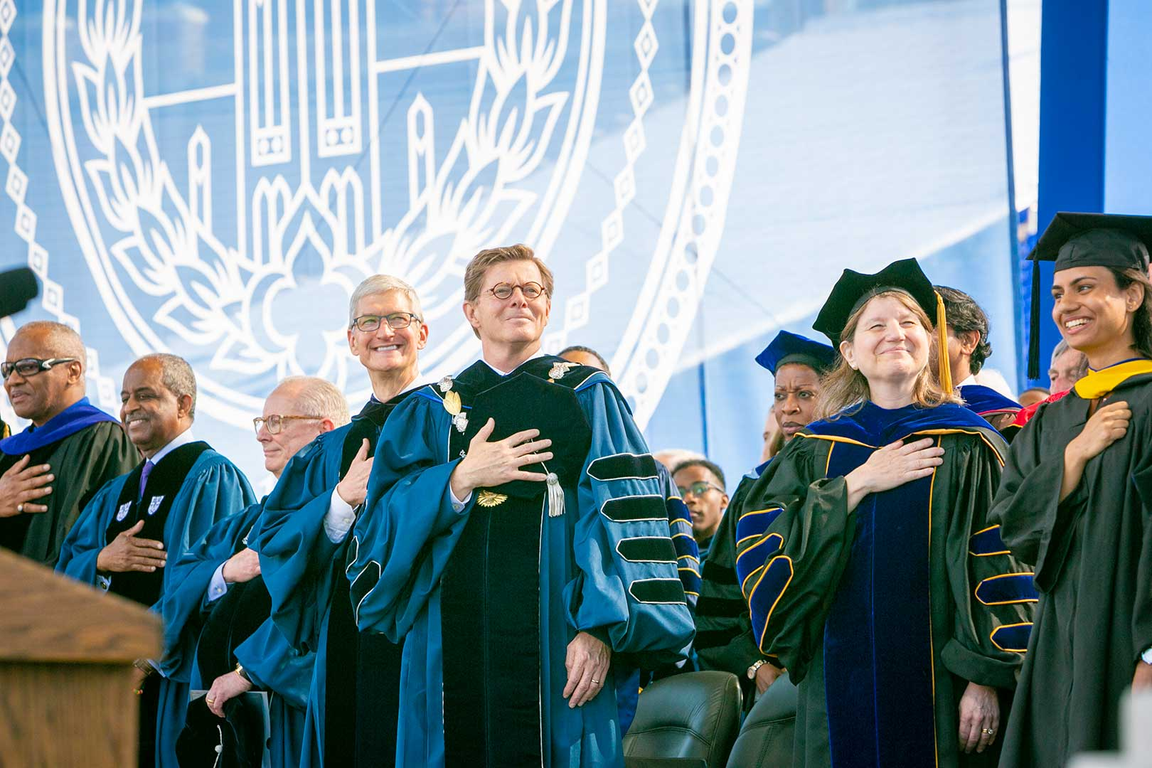 President Vincent E. Price, Provost Sally Kornbluth and keynote speaker & Apple CEO Tim Cook, stand for the national anthem during Duke University's 166th Commencement, at Brooks Field at Wallace Wade Stadium.