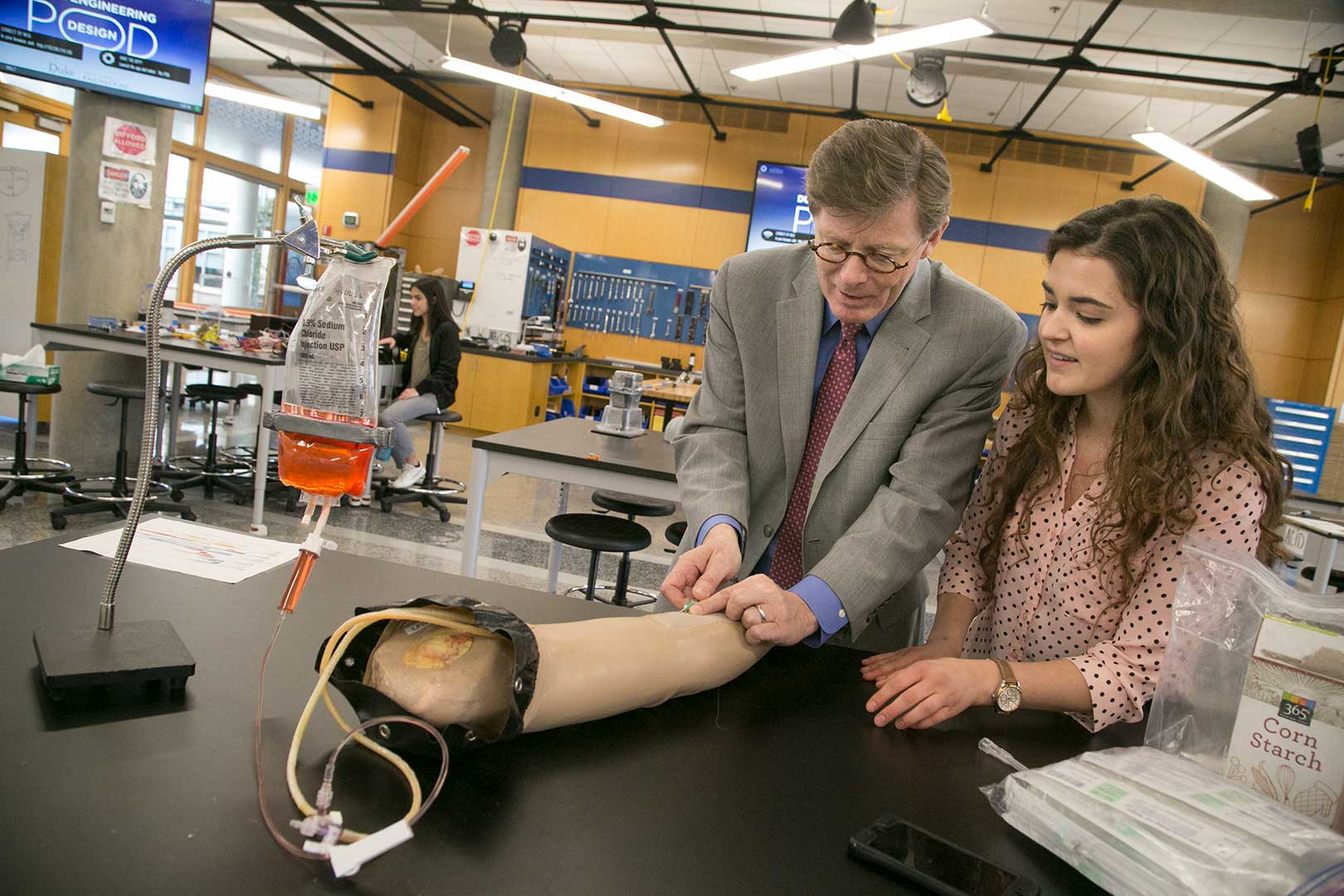 Vincent E. Price visits with a student working on a prosthetic arm at the Pratt School of Engineering's Design Pod.