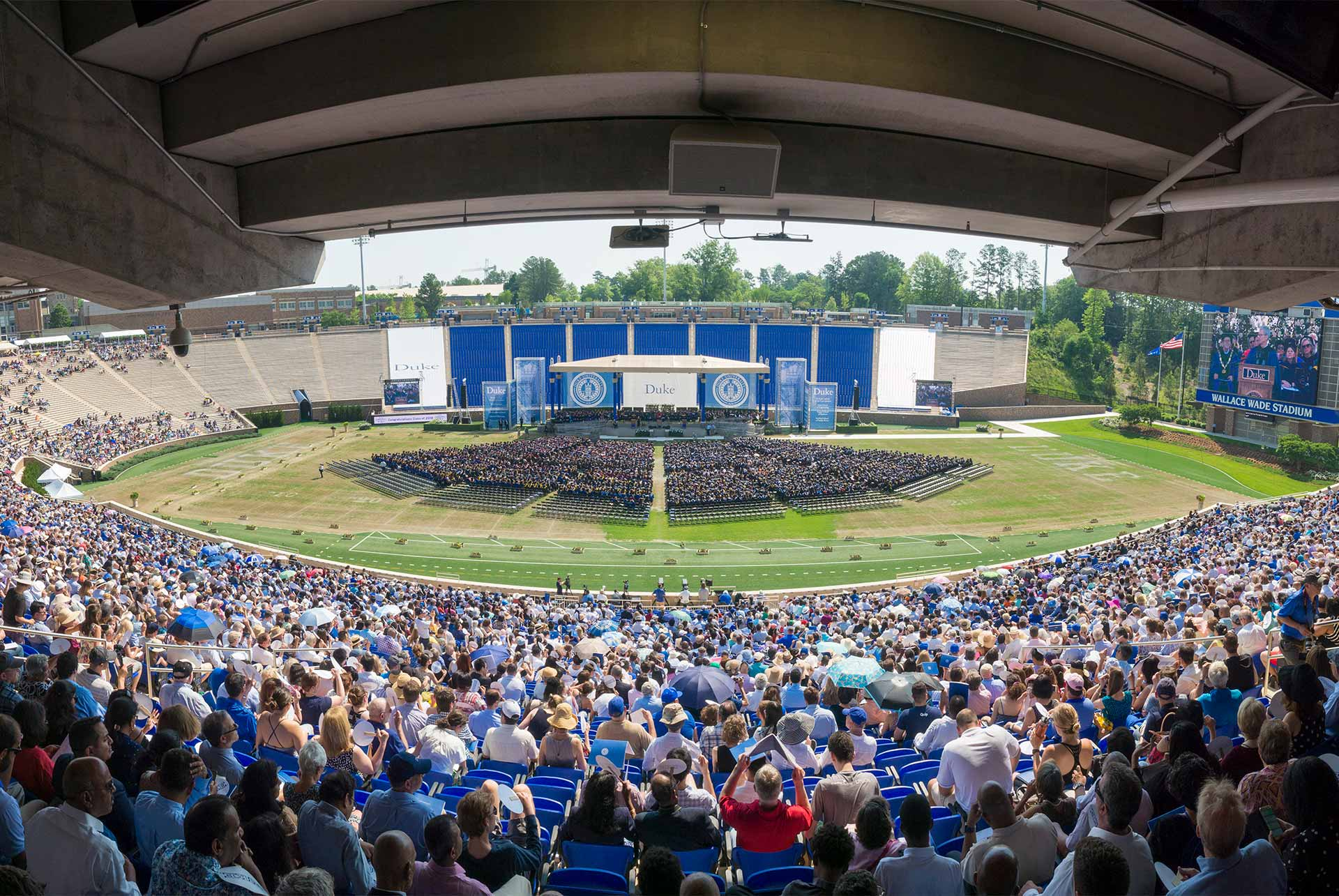 Panoramic photo of the stage and crowd at 2018 Duke University 166th Commencement, Sunday May 13th, 9am at Brooks Field at Wallace Wade Stadium.