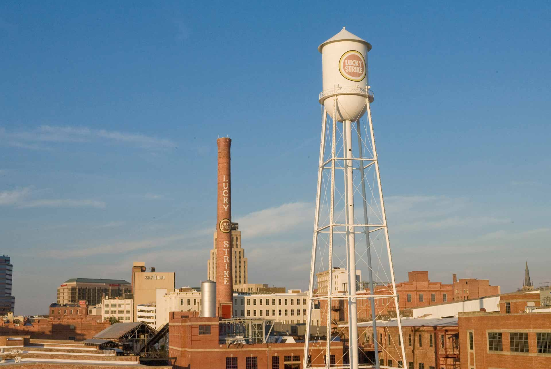 The Lucky Strike smokestack and water tower stand in the foreground against the downtown Durham skyline.